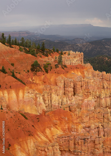 Keuken foto achterwand Rood traf. Orange and yellow cliffs topped with green pines under a cloudy sky in Bryce Canyon national park