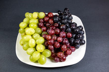 Black, Red, Green Seedless Grapes In A Deep White Bowl On A White Tale Waiting To Be Eaten