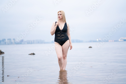 beautiful European plus size girl posing in black swimsuit on the beach alone Tablou Canvas