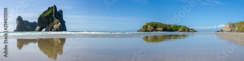 Panoramic view of the Archway Islands reflected in the wet sand at low tide at Wharariki Beach at the northern tip of the South Island of New Zealand.