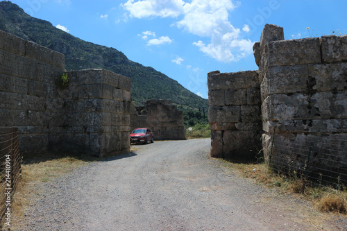 Fotografering  Red car in Arcadian gate, ancient Messini, Peloponnese, Greece