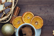 Top view of Christmas balls and cup of coffee.Christmas cookies and dry oranges on a brown wooden table.