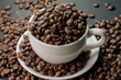 coffee in cup and coffee beans are the background.