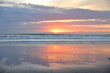 Spiegelung im Wasser am Sandstrand in Muriwai Beach