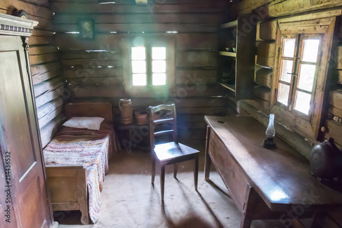 Photo Stands Library A tiny room in a wooden hut. The room has a wooden table, a chair and everything else. Sunshine through the walls