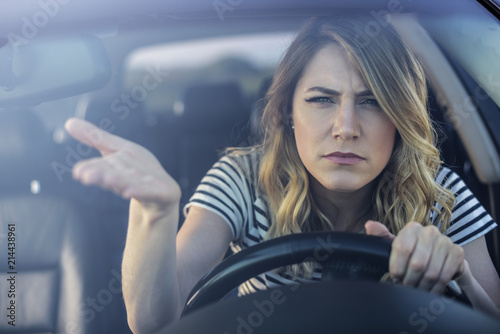 Angry woman driving a car. Fototapet