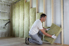 Worker In Protective Goggles And Respirator Insulating Rock Wool Insulation In Wooden Frame For Future House Walls For Cold Barrier. Comfortable Warm Home, Economy, Construction And Renovation Concept