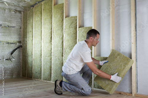 Obraz Worker in protective goggles and respirator insulating rock wool insulation in wooden frame for future house walls for cold barrier. Comfortable warm home, economy, construction and renovation concept - fototapety do salonu