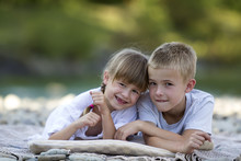 Two Young Happy Cute Blond Smiling Children, Boy And Girl, Brother And Sister Laying Embraced On Pebbled Beach On Blurred Bright Sunny Summer Day Background. Friendship And Perfect Holiday Concept.