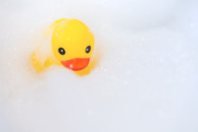 One Yellow Rubber Duck With Soap Bubble Bath, Light  Background With Bubbles. Kids Spa Concept. Children`s Bath Time Concept.