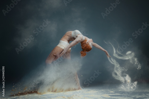 Dancing in flour concept. Redhead beauty female girl adult woman dancer in dust / fog. Girl wearing white top and shorts making dance element in flour cloud on isolated grey black background