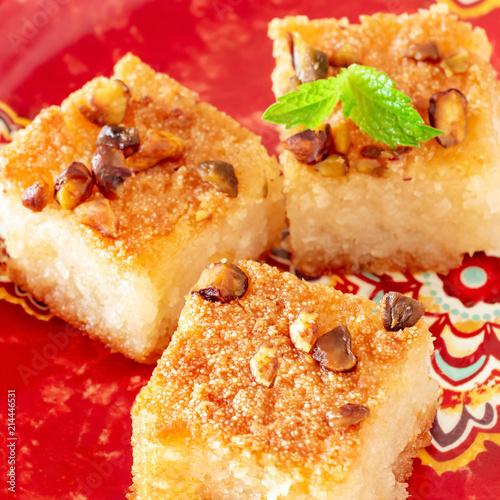 Traditional arabic semolina cake Basbousa or Namoora with nuts and coconut. Close-up. Selective focus. Square photo.