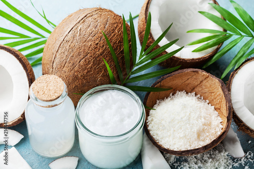 Set of organic coconut products for spa, cosmetic or food ingredients decorated palm leaves. Coconut oil, water and shavings.