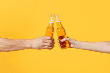 Close Up Cropped Of Woman And Man Two Hands Horizontal Holding Lager Beer Glass Bottles And Clinking Isolated On Yellow Background. Sport Fans Cheer Up. Friends Leisure Lifestyle Concept. Copy Space.