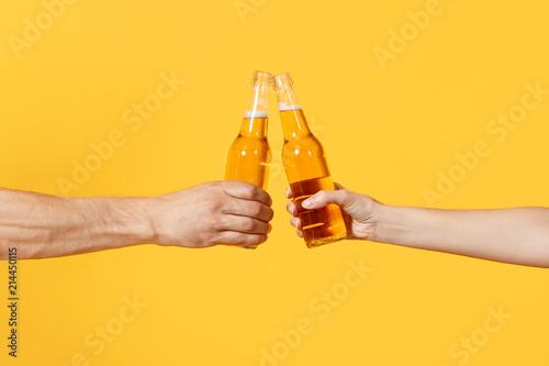 Valokuva Close up cropped of woman and man two hands horizontal holding lager beer glass bottles and clinking isolated on yellow background