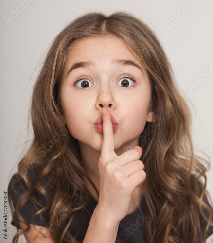 Beautiful little girl with finger on lips f Wall mural