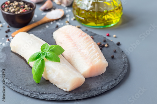 Fotografija Fresh raw cod fillet with spices, pepper, salt, basil on stone plate, horizontal