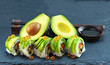 japanese avocado sushi set with shoyu source on black slate dish