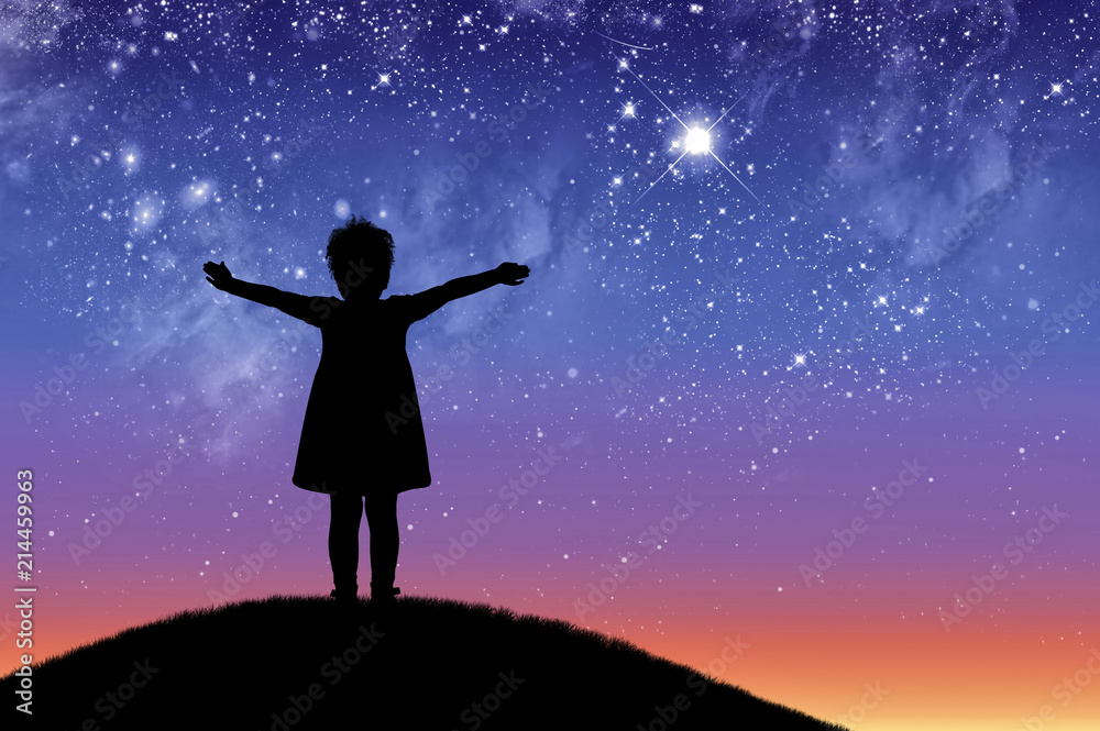 Silhouette, little happy girl child standing on a hill looking not starry beautiful sky.