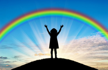 Silhouette of a happy little girl child with raised arms trying to touch the rainbow