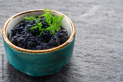 Black lumpfish caviar in a small pot on dark backgournd