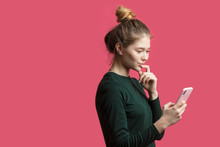 Attractive Hipster Girl Wearing Hairbun, Using Her Smartphone For Reading News In Social Public
