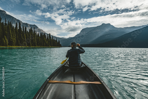Valokuvatapetti Young Man Canoeing on Emerald Lake in the rocky mountains canada with canoe and mountains in the background blue water