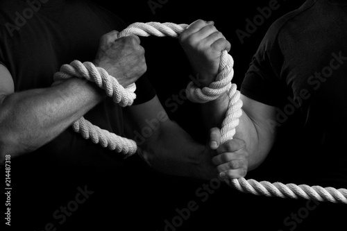 Foto  Men tighten a rope on a black background