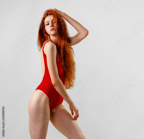 b90d3d4b569 Young sexy slim woman in red swimsuit posing in studio. Full length fashion  portrait of beautiful girl with long wavy red hair. Swimwear or bikini mode.