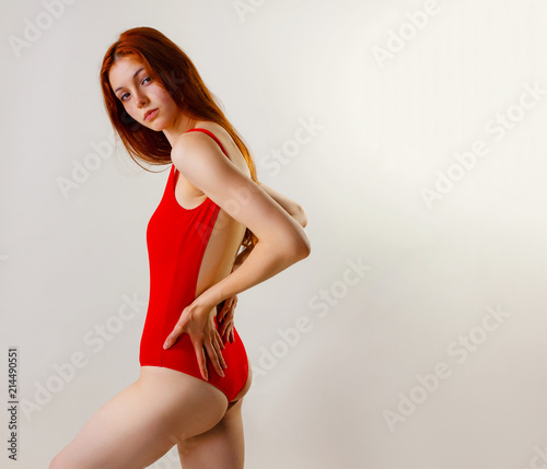 70cd1501e7a Young sexy slim woman in red swimsuit posing in studio. Full length fashion  portrait of