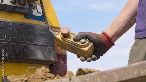 Obraz Geotechnical investigation - a hand holding a crane control button - fototapety do salonu
