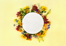 Creative Decoration Summer Flowers Sunflowers, Calendula, Linaria, Chamomiles, Blue Cornflowers With Circle Paper Card Note With Space For Tex On Yellow Paper Backgroundt. Top View, Flat Lay