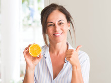 Middle Aged Woman Holding Orange Fruit Happy With Big Smile Doing Ok Sign, Thumb Up With Fingers, Excellent Sign