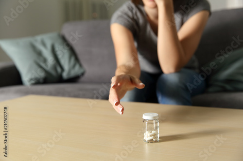 Woman hand reaching a bottle of painkiller capsules