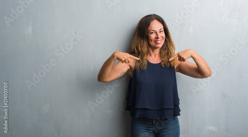 Fotografie, Obraz  Middle age hispanic woman standing over grey grunge wall looking confident with smile on face, pointing oneself with fingers proud and happy