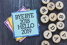 Handwriting Text Bye Bye 2018 Hello 2019. Concept Meaning Starting New Year Motivational Message 2018 Is Over Black Wooden Deck Written Sticky Note Beside Some Round Woody Alphabets.