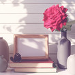 A fresh red rose with drops of water on the petals is in a gray vase. Nearby is a stack of books, a photo frame and a black cat figure. White wooden background