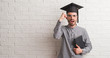 Young adult man over brick wall wearing graduation cap annoyed and frustrated shouting with anger, crazy and yelling with raised hand, anger concept