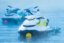 Three Jet Skis Are Moored On A Frosty Cold Lake. They Are Covered With Fresh Snow On A Winter Morning.
