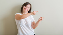 Down Syndrome Woman Standing Over Wall Smiling And Looking At The Camera Pointing With Two Hands And Fingers To The Side.