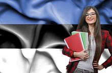 Happy Female Student Holdimg Books Against National Flag Of Estonia
