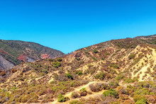 Bright Summer Morning In Southern California Mountains With Fire Damage And Fire Retardant Covering Hills