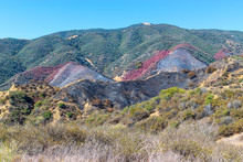 Dry Brush In The Hills Of Southern California Mountains With Burned Hillsides And Red Fire Retardant In The Middle Of Forest