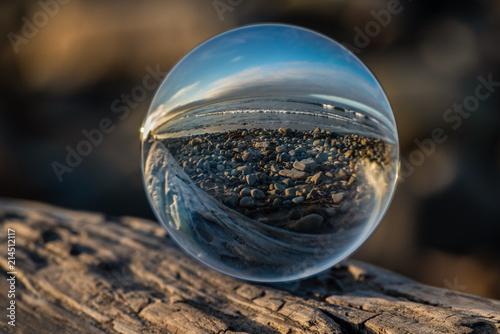 Obraz na plátně  Cobblestone shoreline of the beach distorted by the spherical lens on textured driftwood