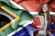 canvas print picture - Happy female student holdimg books against national flag of South Africa