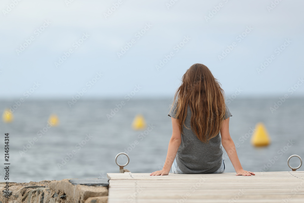 Fototapeta Back view of a lonely teen looking at the ocean