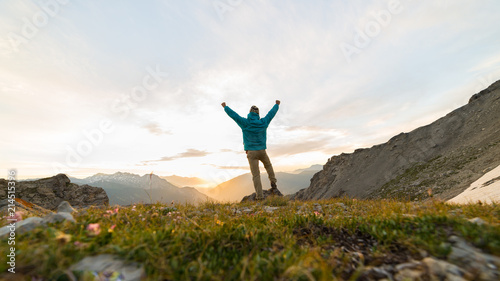 Photo Man standing on mountain top outstretching arms, sunrise light colorful sky scenis landscape, conquering success leader concept