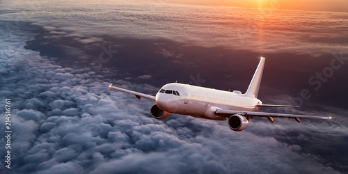 Commercial airplane flying above dramatic clouds. Canvas Print