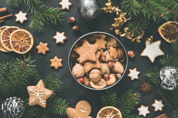 New Year or Christmas box with sweets Gingerbread cookies, gingerbread stars, dried orange rings and fir tree. Top view. Christmas flat lay composition