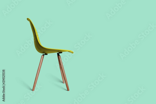 Fotografia Modern yellow retro chair on a green pastel background